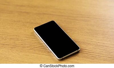 smartphone with blank black screen on wooden table -...