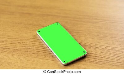 smartphone with blank green screen on wooden table -...