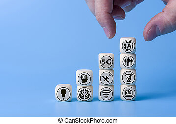 Technology concept with icons on wooden cubes, blue background.