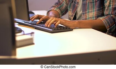 hands typing on computer keyboard at night office -...