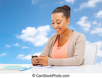 african student girl with smartphone and notebooks