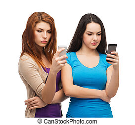 two serious teenagers with smartphones - technology, ...