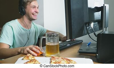 technology, games, entertainment, play and people concept. a young man playing a computer game at home, drinking beer and eating pizza. 4k, slow motion