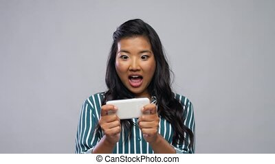 happy asian woman playing game on smartphone