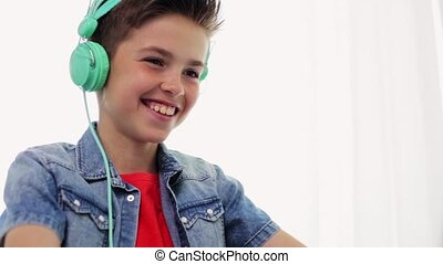 happy boy in headphones laughing at home - technology,...