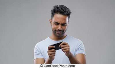 happy indian man playing game on smartphone