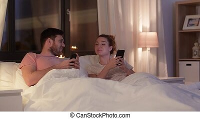happy couple using smartphones in bed at night - technology,...