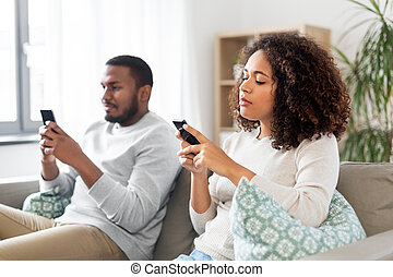 african american couple with smartphone at home