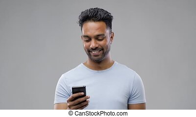 happy indian man with smartphone - technology, internet,...