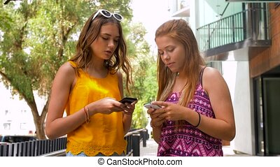 teenage girls with smartphones in summer city - technology,...