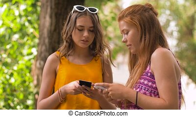 teenage girls with smartphones in summer park - technology,...