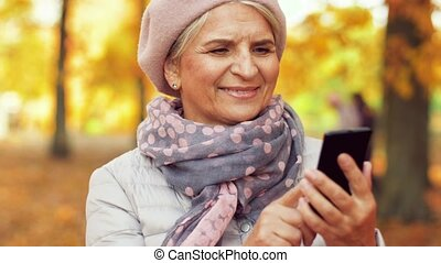 happy senior woman with smartphone at autumn park