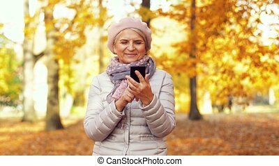 happy senior woman with smartphone at autumn park -...
