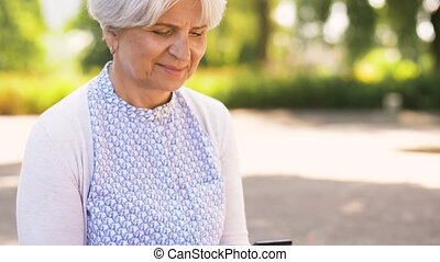 happy senior woman with smartphone at summer park