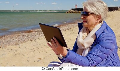 senior woman with tablet computer on beach - technology, old...