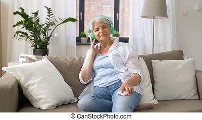 senior woman in headphones listening to music - technology,...