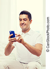 happy man with smartphone at home