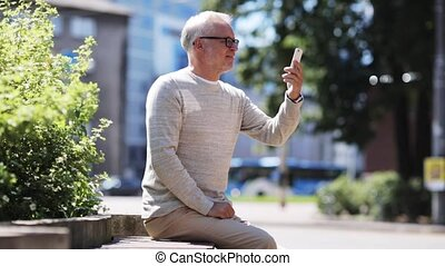 senior man having video call on smartphone in city