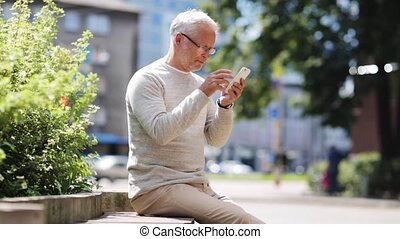 senior man texting message on smartphone in city