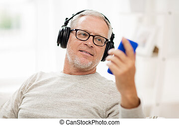 happy senior man with smartphone and headphones - technology...