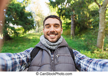 happy man with backpack taking selfie and hiking