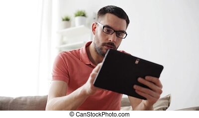 man with tablet pc tired from eyeglasses at home -...