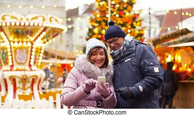 senior couple with smartphone at christmas market