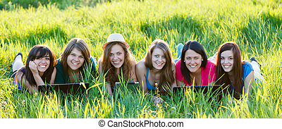 Beautiful girls using their laptops and tablet outdoors on grass.