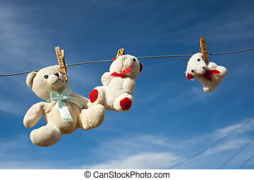 Three teddies hung out to dry on a clothesline, with blue skies in the background