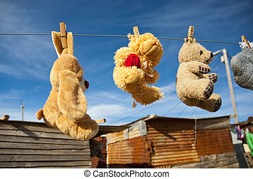 Various teddies hung out to dry in front of shack in a township in South Africa