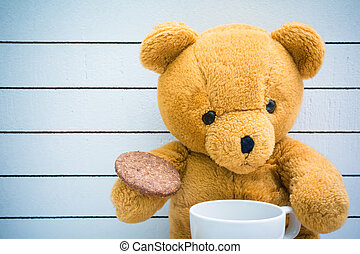 Teddy bear drink milk with cookies on a wooden background