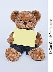Teddy bear holding a blank sign
