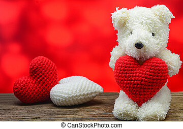 Teddy bear holding a heart-shaped on wooden table