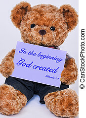 Teddy bear holding a  sign that says In the beginning God created