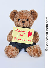 Teddy bear holding a yellow sign saying Missing my sweetheart