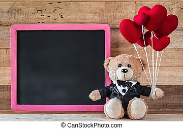 Teddy bear holding heart-shaped balloon