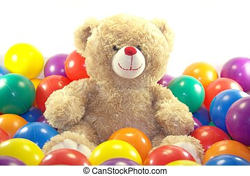 Teddy bear is playing with colorful balls