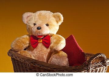 teddy bear is sitting in the wicker basket