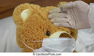 Teddy bear measure the temperature by hand closeup. The doctor makes a measurement of temperature by applying a hand to his forehead. The bear lies in bed with a medical mask.