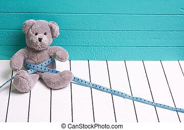 Teddy bear on a white wooden floor blue-green background with centimeter. Diet and weight loss in children