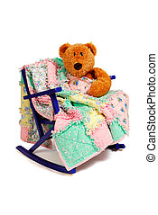 A Teddy Bear sits in a vintage child's chair, compforted with a rag quilt.