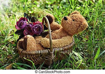 teddy bear sitting in a wicker basket