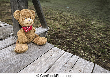 Teddy bear sitting on a pier