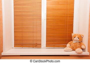 teddy bear sitting on the window