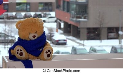 Teddy bear with blue scarf is sitting by window in winter. Snowflakes falling