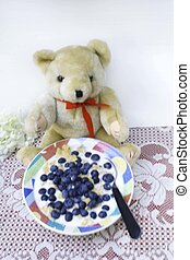 Teddy bear with bowl of blueberries and milk