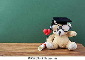 Teddy bear with graduation hat and diploma in front of green chalkboard. School concept