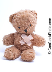 An old, 1960s teddy bear with plasters in an 'x' shape over his heart to represent either injury or lost love.