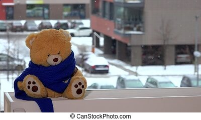 Teddy bear with scarf sitting on radiator near window. Child take toy friend