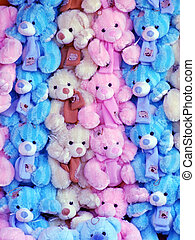 Lots of colorful teddy bears at a fairground stall,
